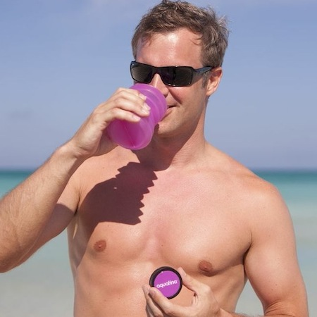 naked man by the sea drinking from a reusable drinking bottle