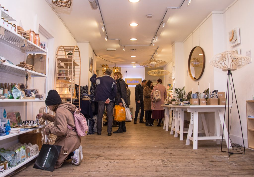 Interior of Blue Patch's pop-up Christmas shop in Shoreditch, showing woman looking at products, wearing a black hat. More people talking and shopping in the background.