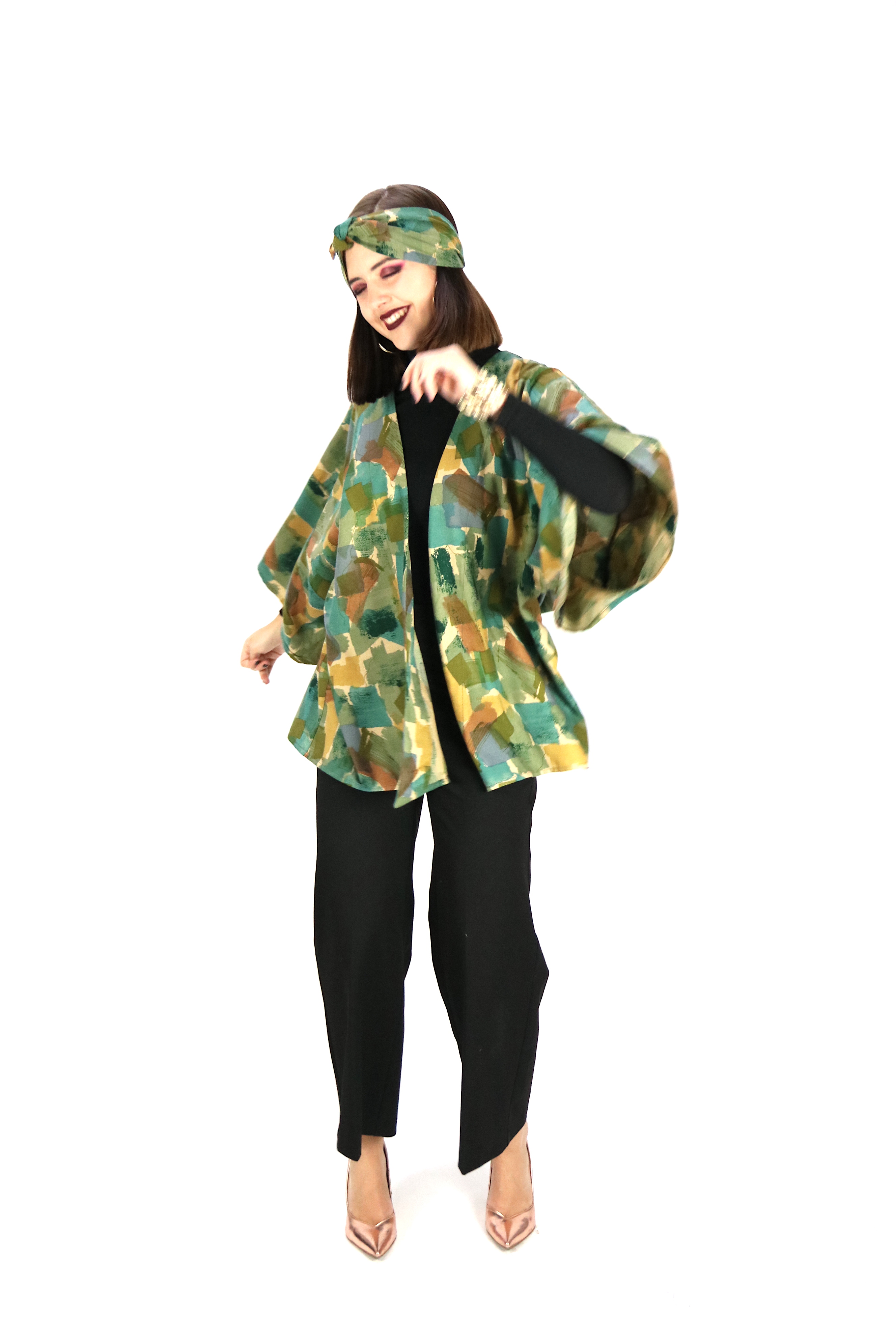 woman wearing a jacket and matching headband in mottled green tonde, with black trousers