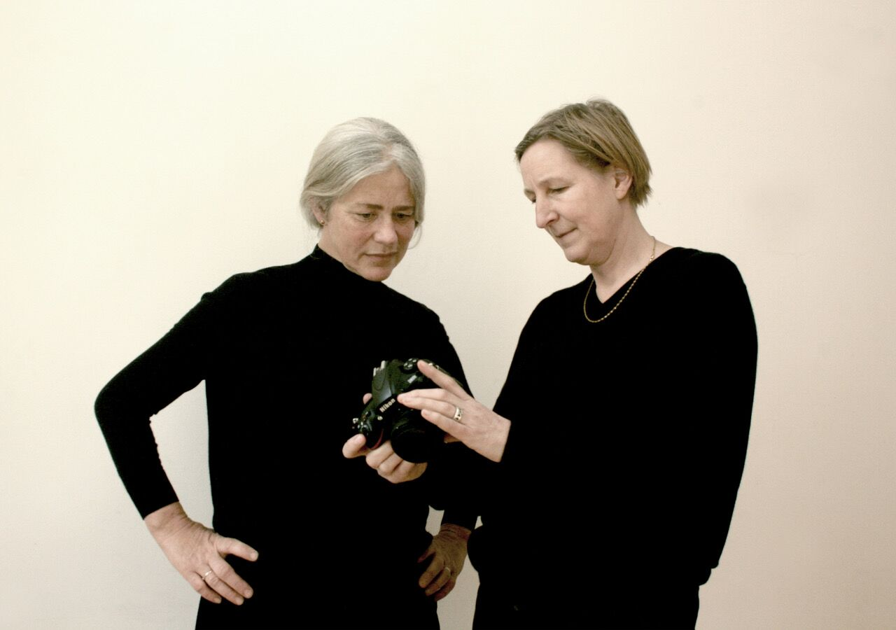two women in black examining a camera