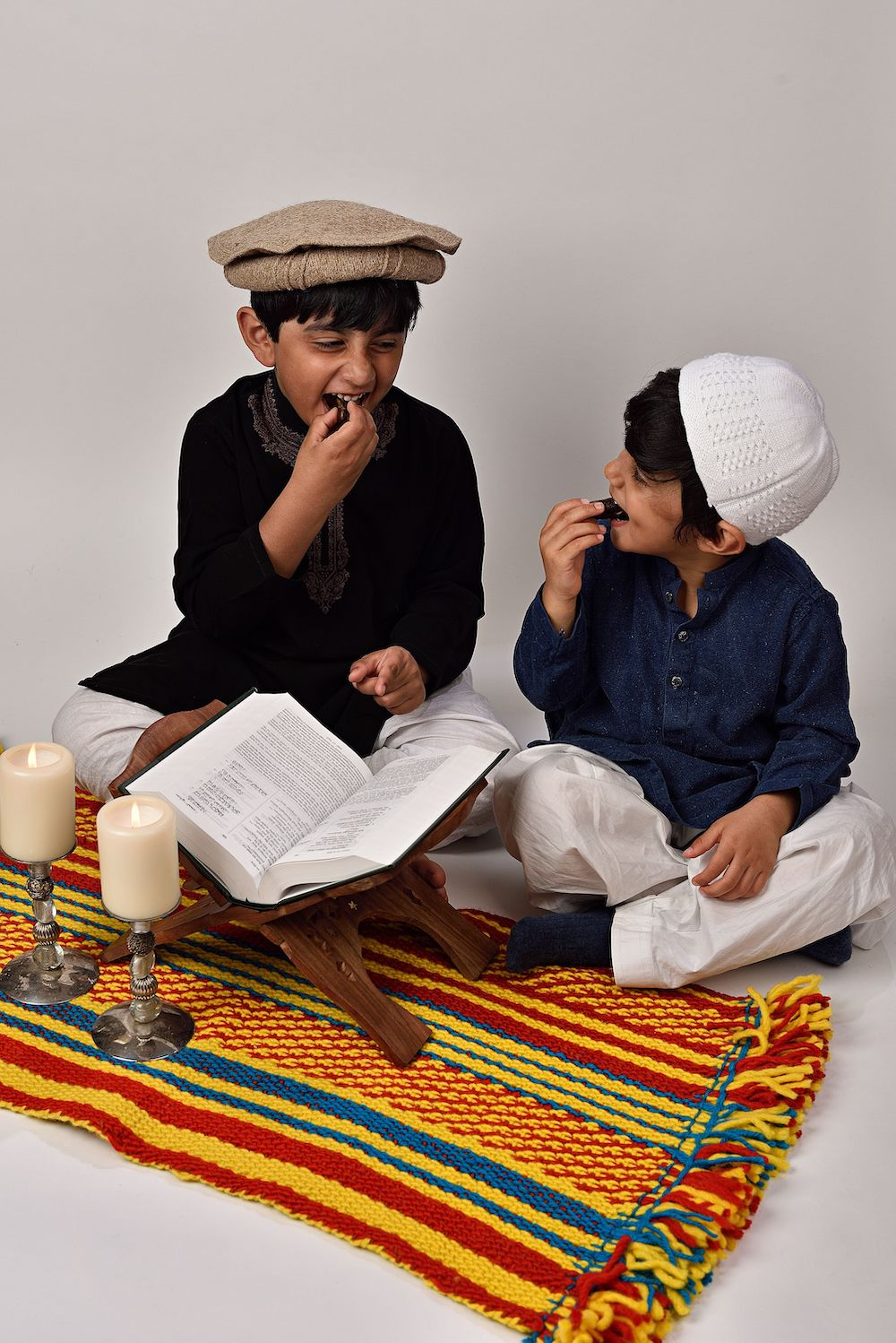 two young boys in hats eating dates on a prayer mat