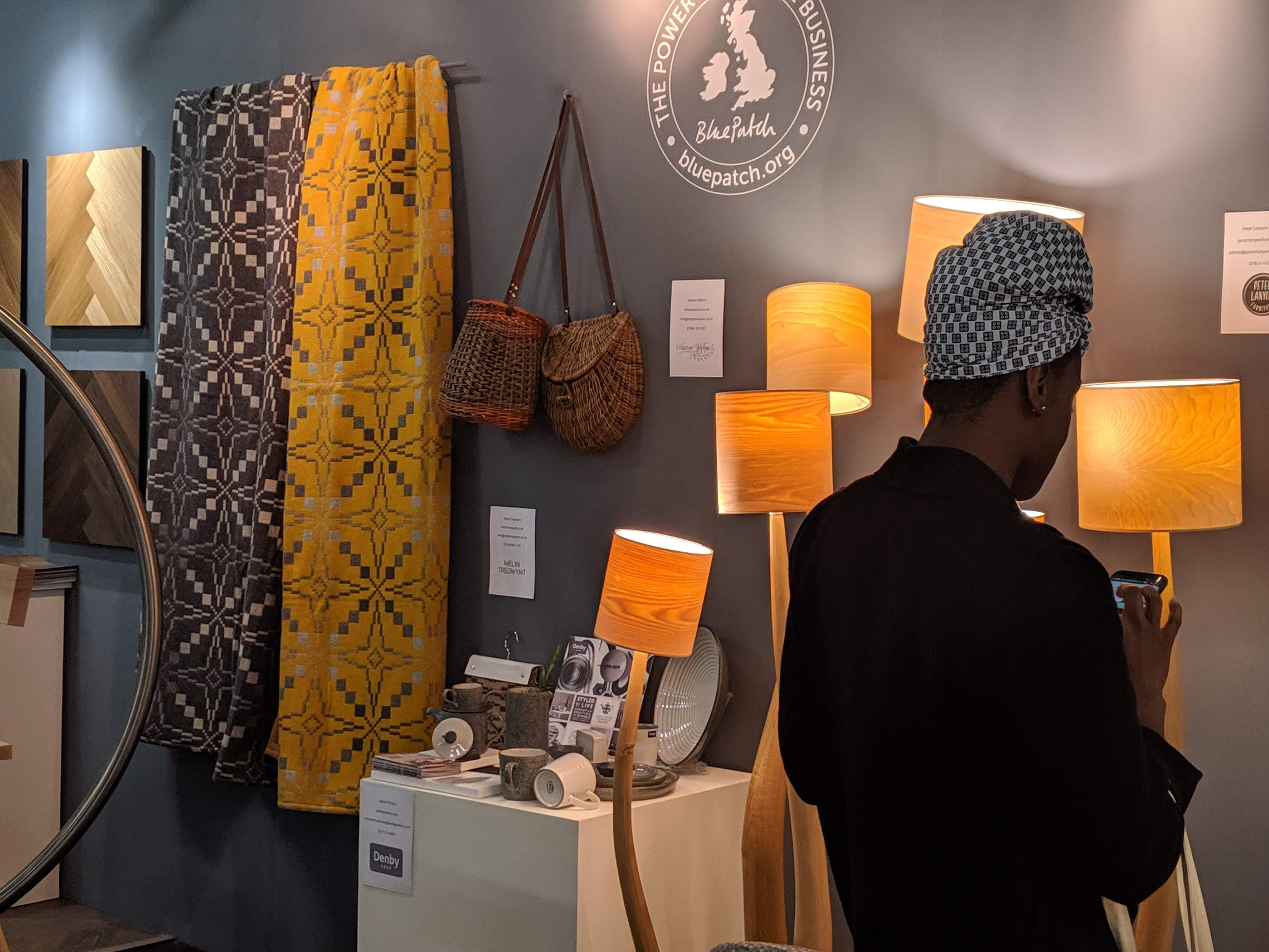 Woman in a headdress texting a message in Instagram, looking at the Blue Patch stand at London Design fair 2019