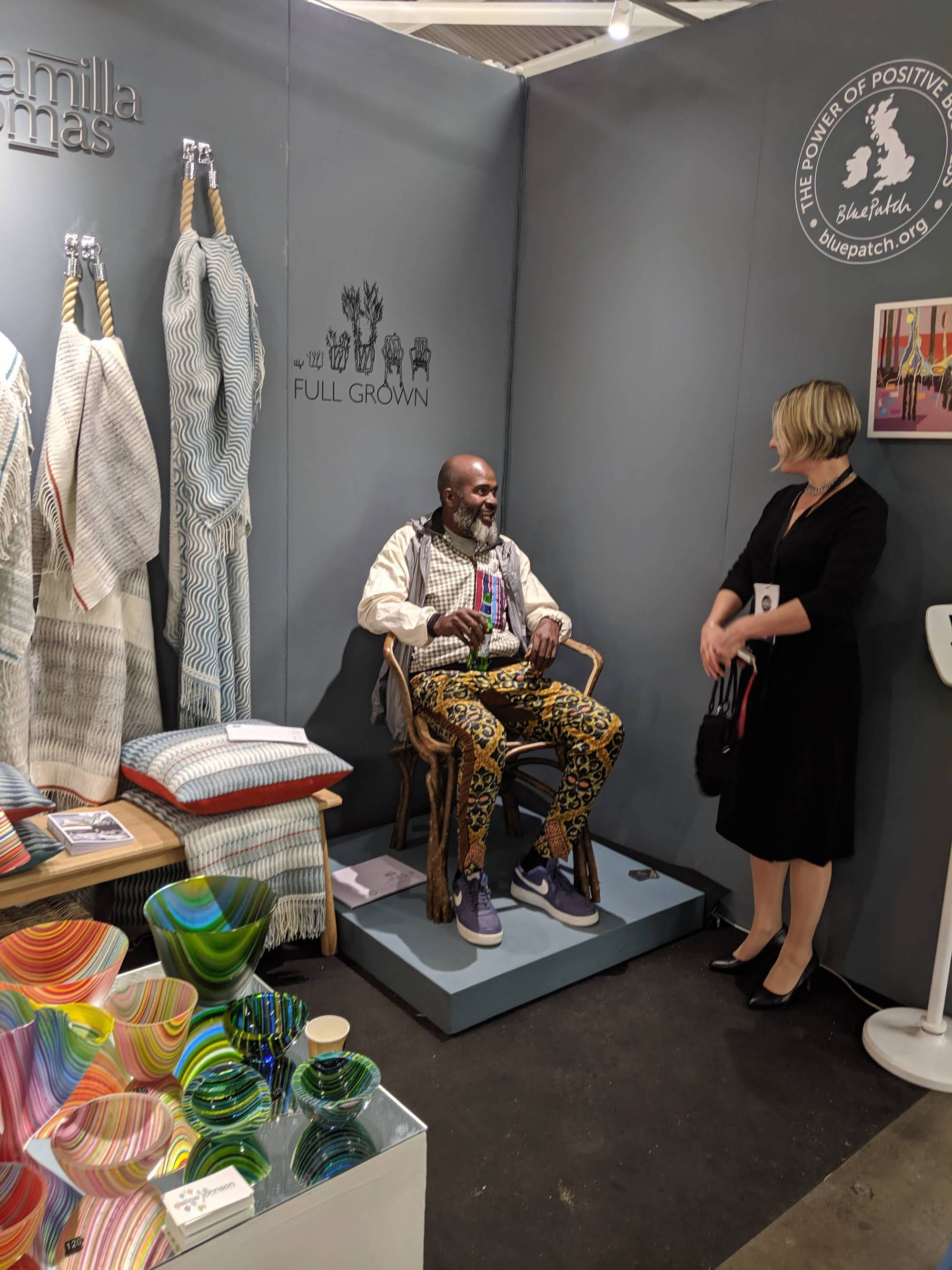 Man sitting down to try a home-grown chair by Full Grown, with colourful glass and blankets in the foreground, at London Design Fair.