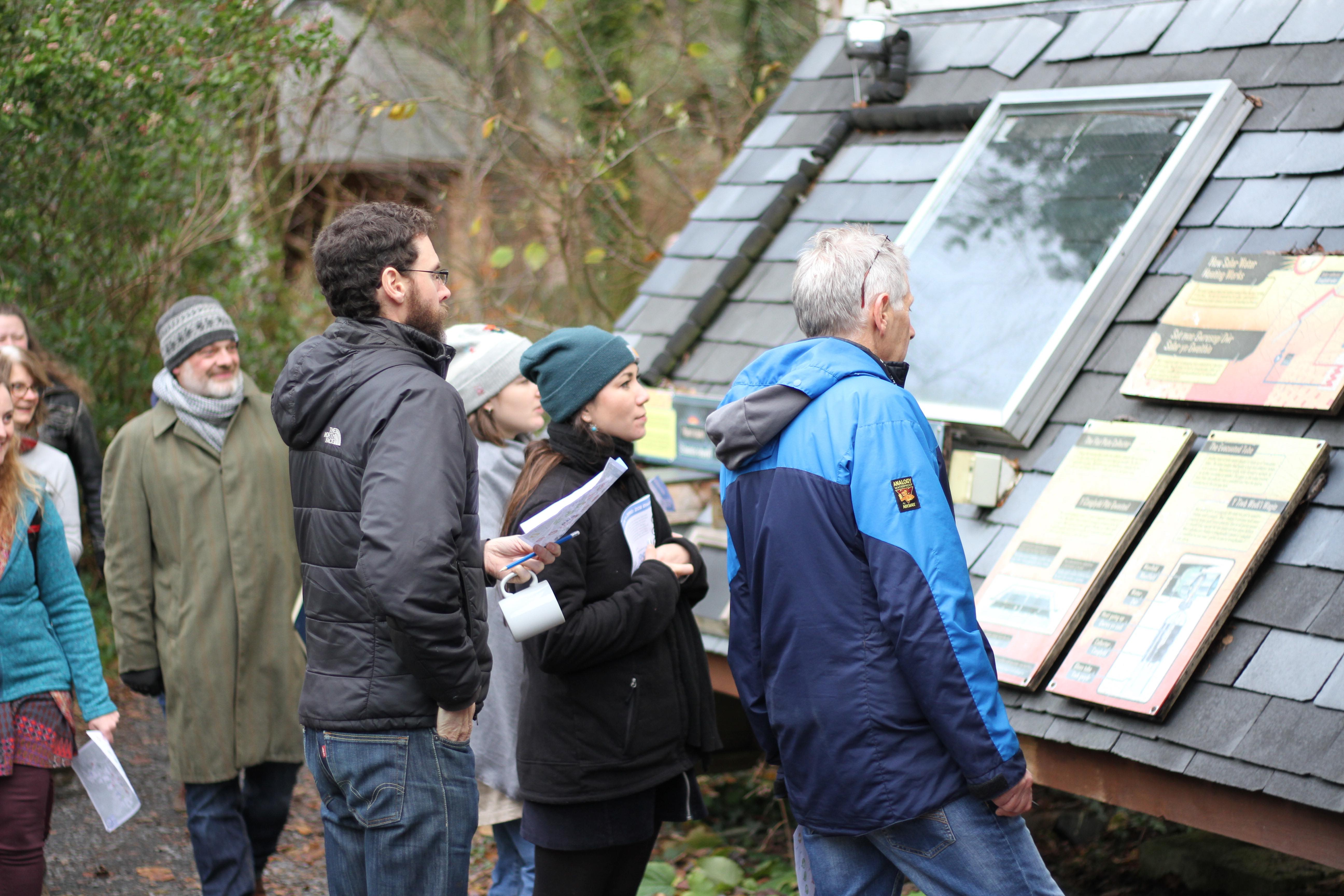 people gathered by a roof, at ground level, learning about heat loss and insulation at the Centre for Alternative Technology