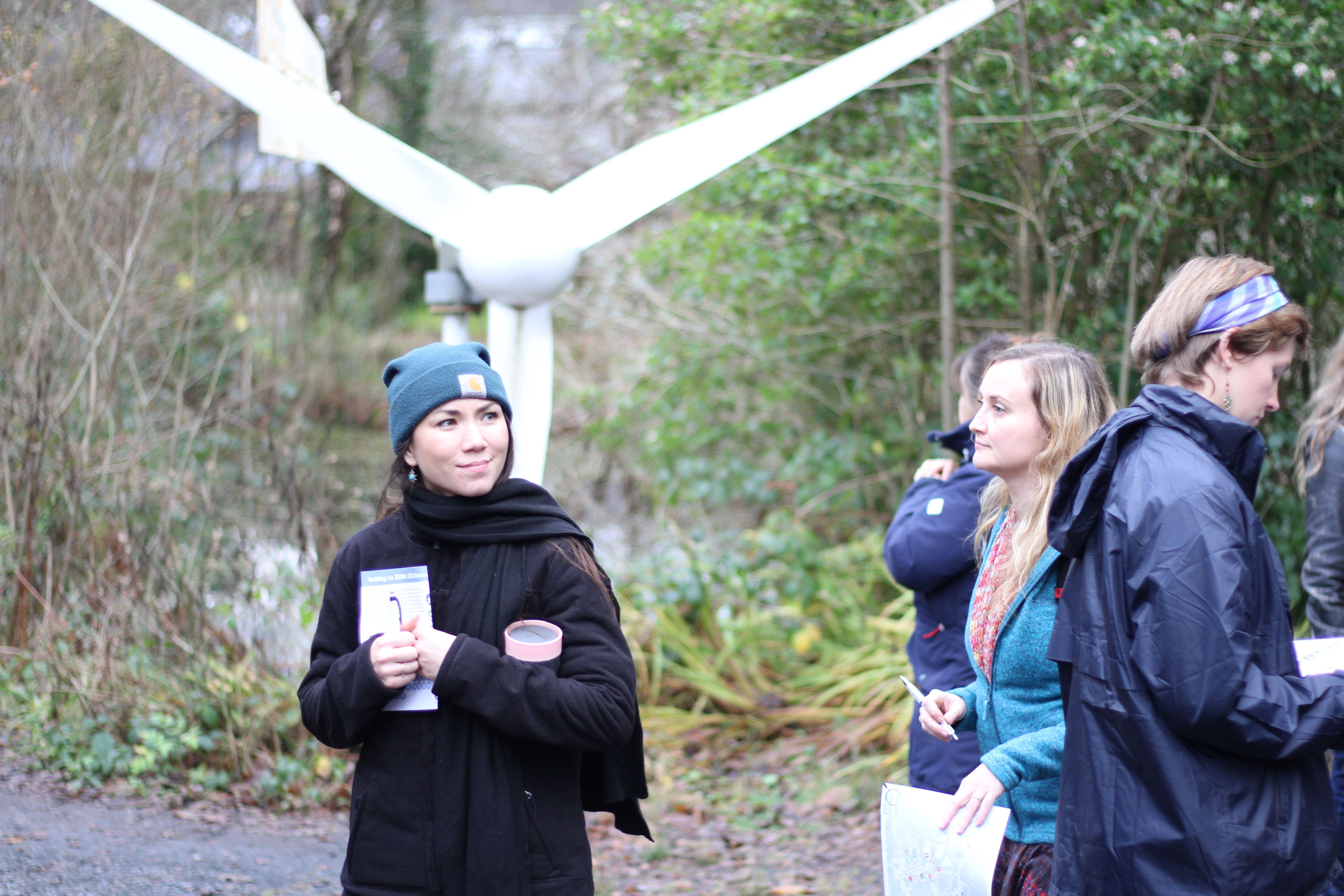 group of four people near a small wind turbine, set in the woods at the Centre for Alternative Technology in Wales