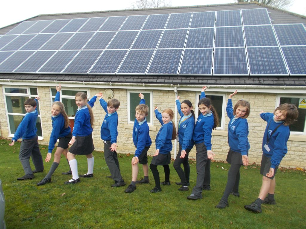 a row of school children showing their solar roof, a project Blue Patch invested in via Ethex