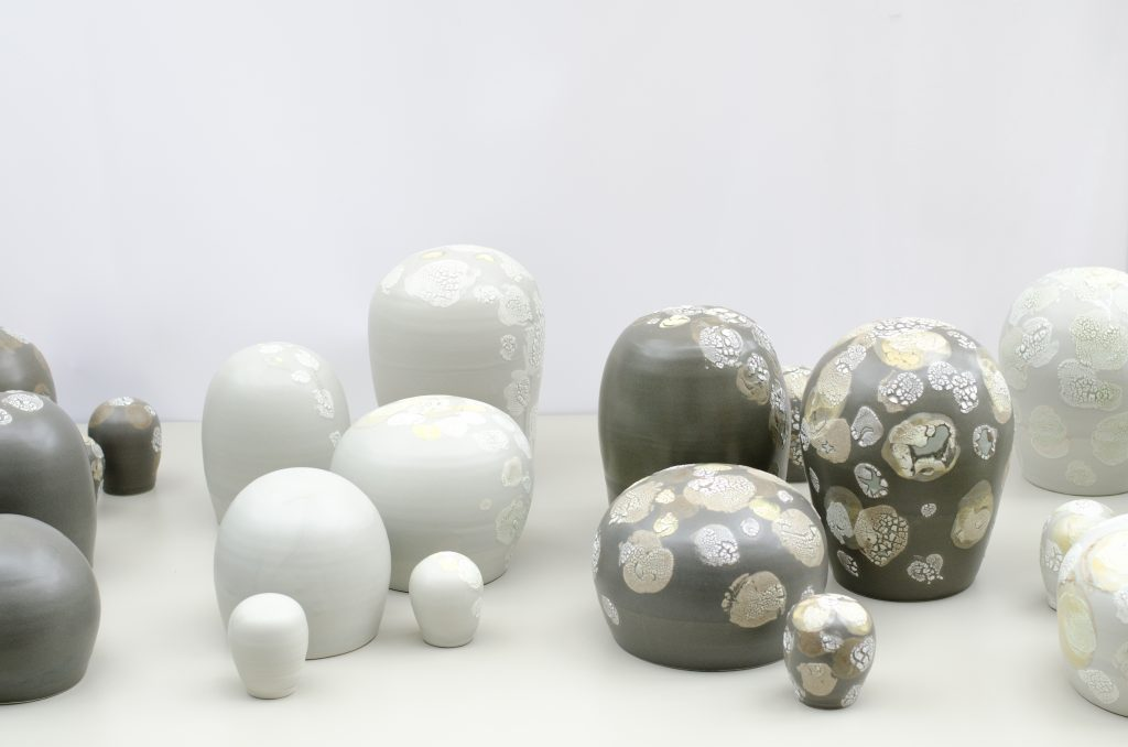 a collection of ceramic domed forms with glazed organic textures in grey and white, on a white table, made by a sustainable local craft business