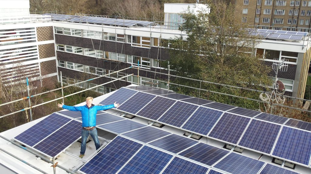 man with arms outstretched, standing on a roof covered with solar panels, showing our investments into solar energy