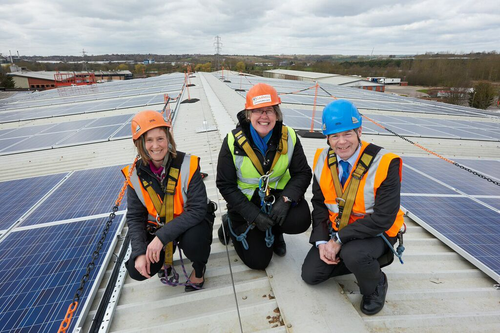three trades people in high vis, kneeling on a roof, with solar panels on it.