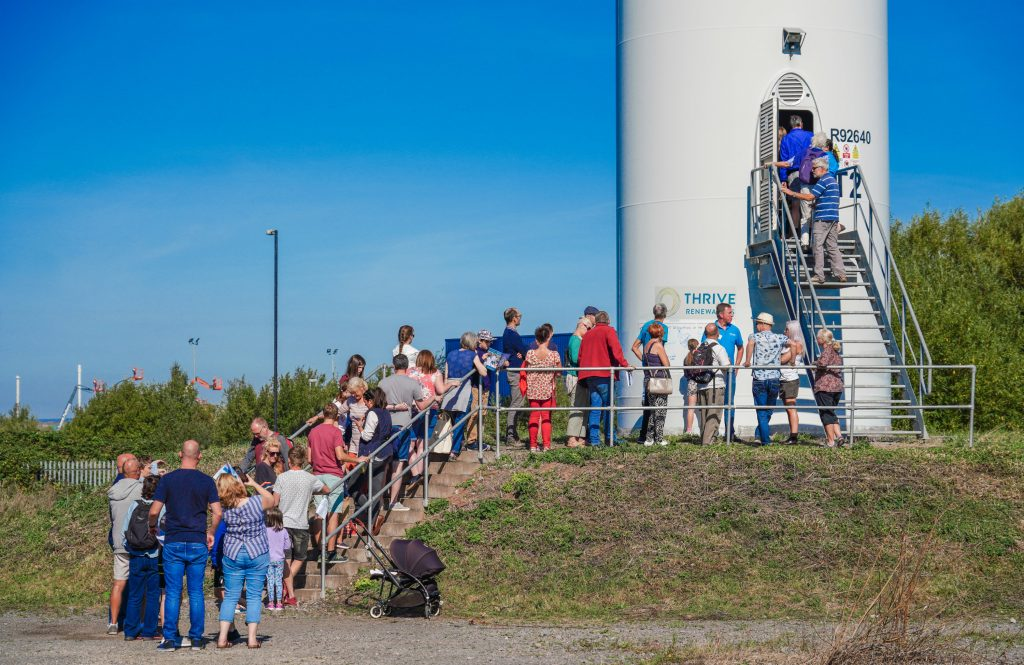 a line of people waiting to visit a wind turbine