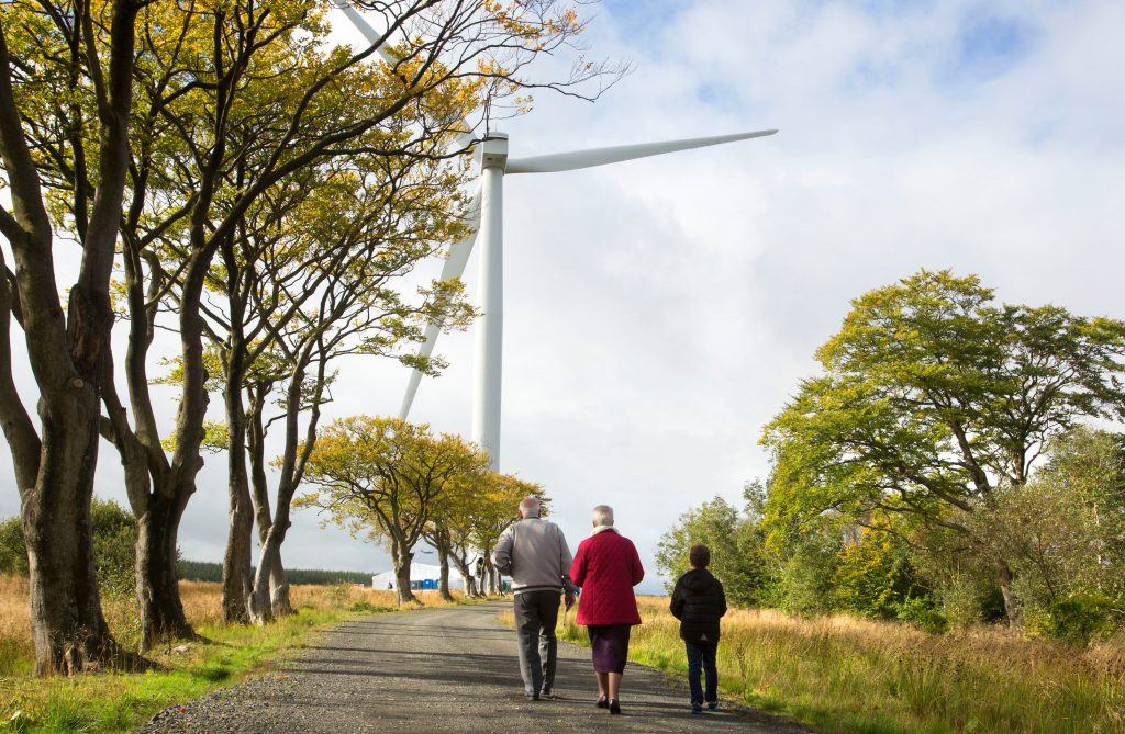 people walking down a country path, with trees and a giant wind turbine, showing our commitment to sustainable and renewable energy