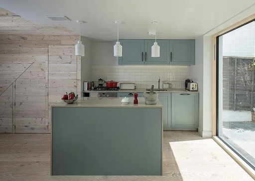 contemporary kitchen with glass doors to a terrace, showing a retrofitted home, that's sustainable and a great advertisement for green living and how to stop climate change.