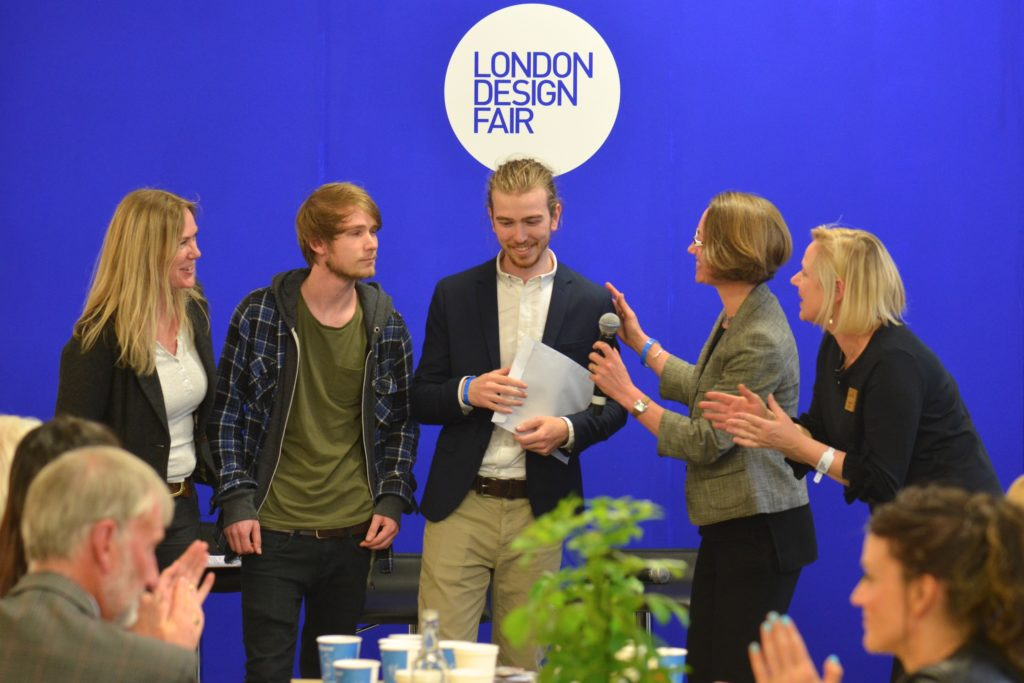five people getting a New Business sustainable business award at London Design Fair, with people in foreground clapping and a royal blue backdrop