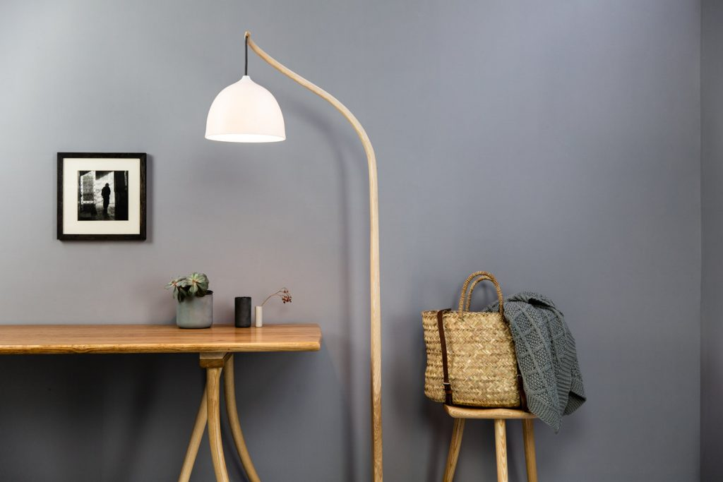 Room with a grey painted wall,  wooden table with plants on, a black and white photo on the wall, a tall lamp with hanging white shade and a stool with basket and blanket set upon it. Showing the work of a UK handcrafter.