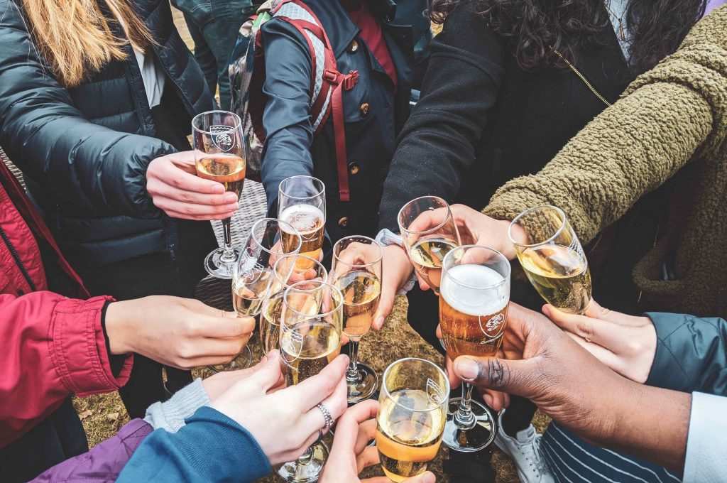Photo of people's hands holding glasses of wine and clinking glasses in celebration