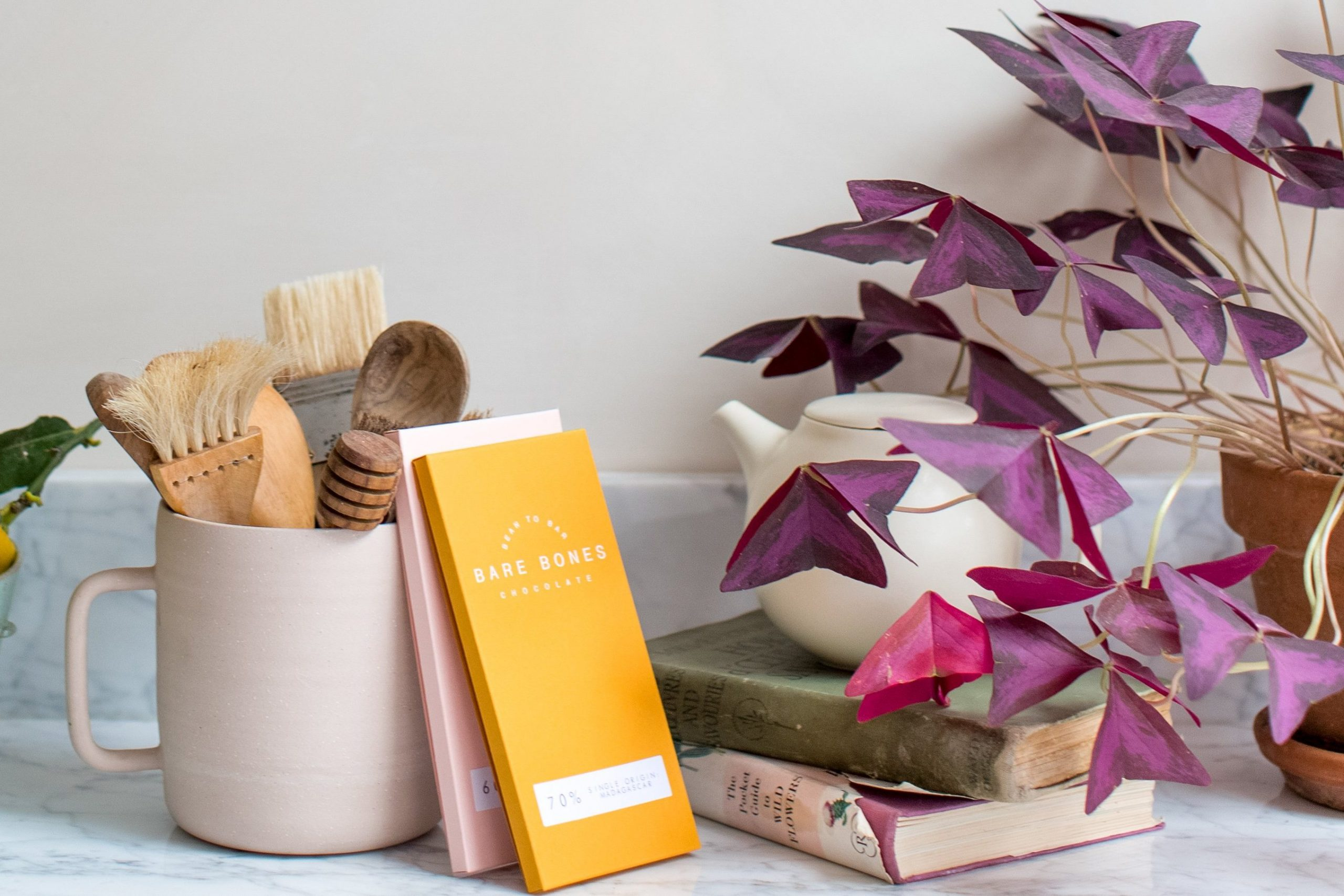 pink mug with brushes in, two chocolate bars wrapped in yellow and pink, books, a tea pot and plant on a kitchen counter