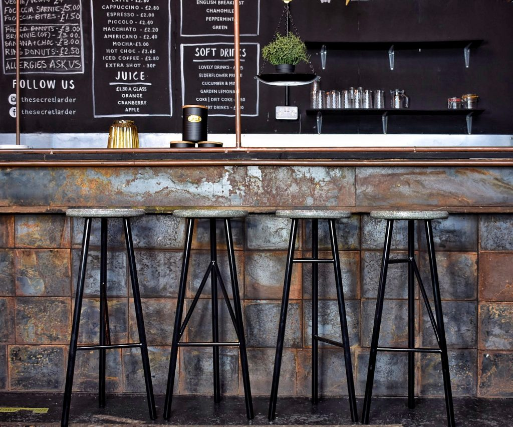 a row of four stools on metal legs with wooden seats, set against a slate tiles bar, with a chalk board with the drinks menu on and some glasses.