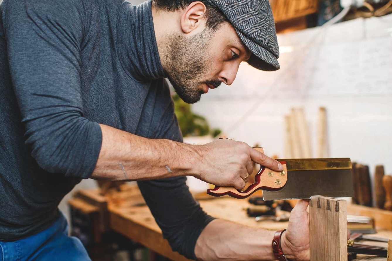 A young man sawing wood, wearing a flat cap and blue jumper. In his wood workshop