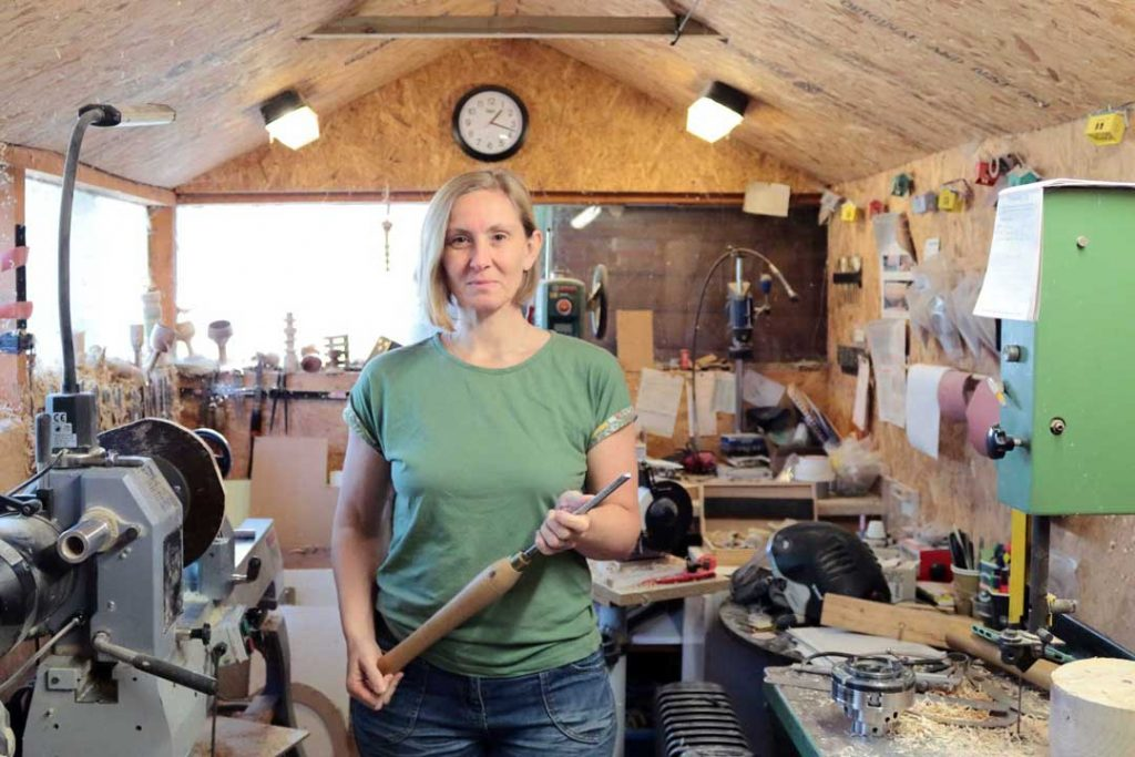 woman in a workshop wearing a green tee shirt with blond bob, holding a tool.