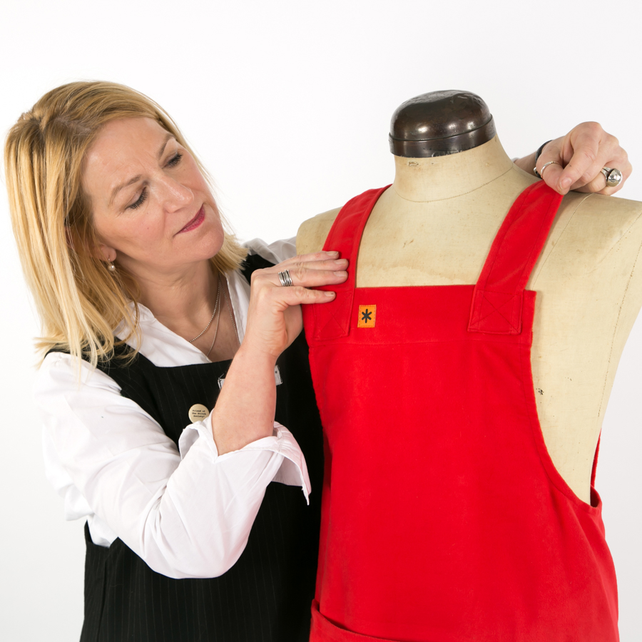 woman in a black apron and white shirt, with a red apron on a tailors dummy