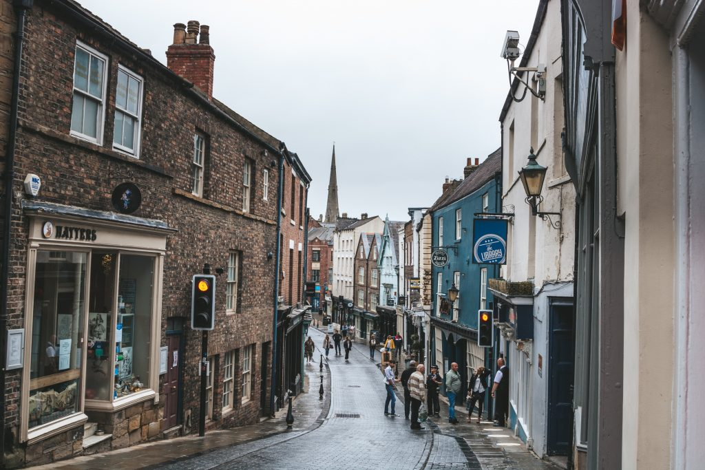 An old fashioned high street with shops and a few people. On a rainy day.