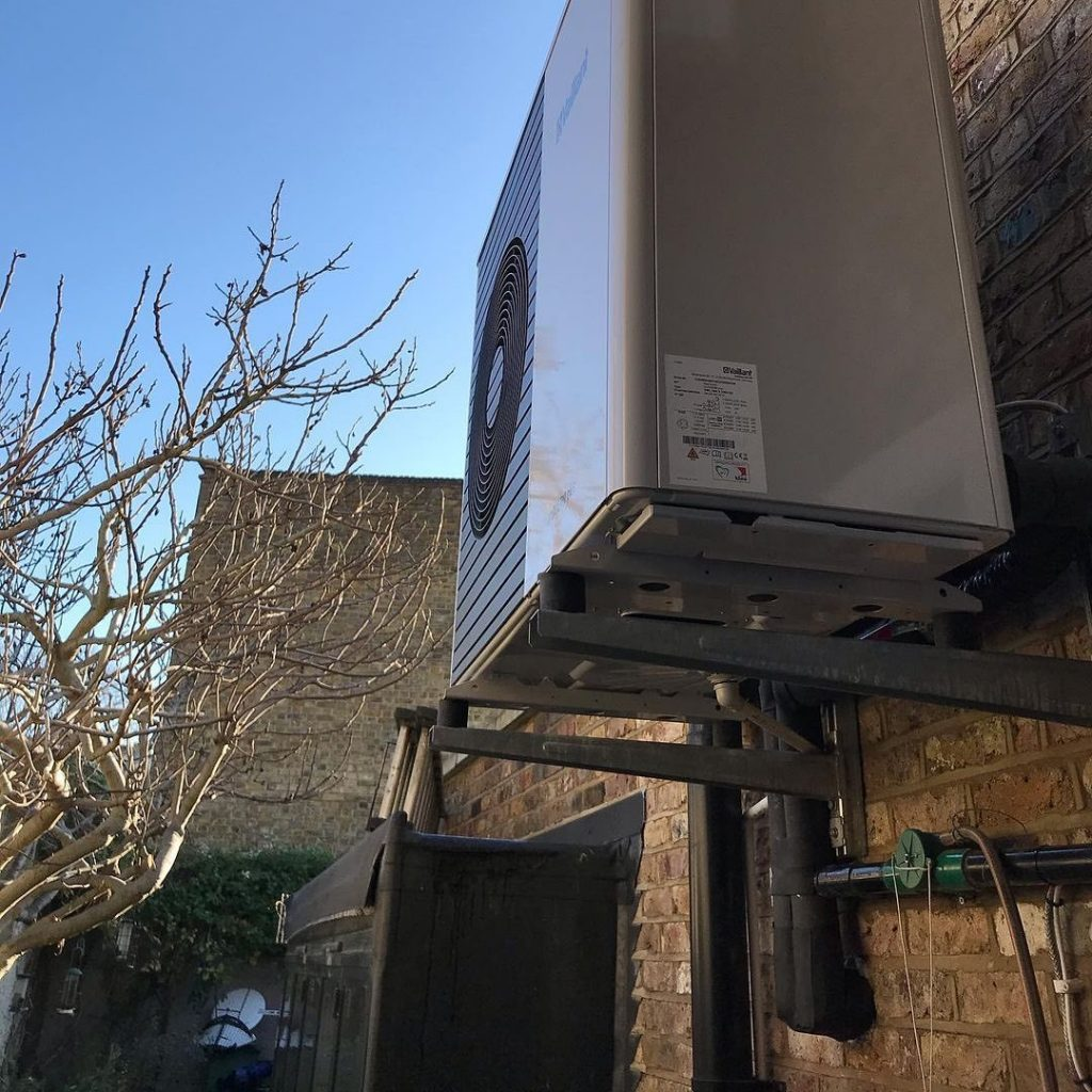 side return of a house with a heat exchanger mounted on the wall, showing climate change mitigation through sustainable building and retrofit