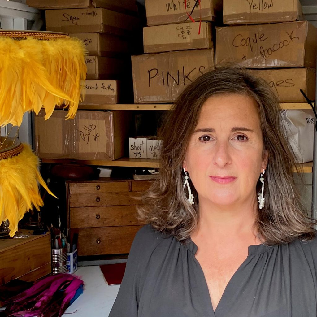 woman in a store room with brown boxes and a set of yellow feathers