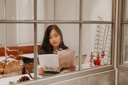 Girl reading through a window