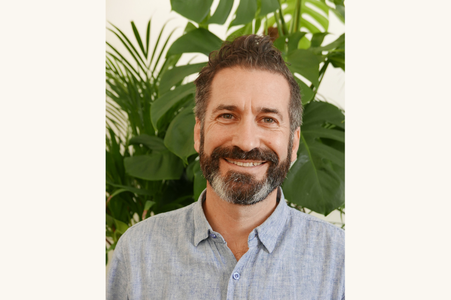 Smiling man with a beard and house plants behind him.