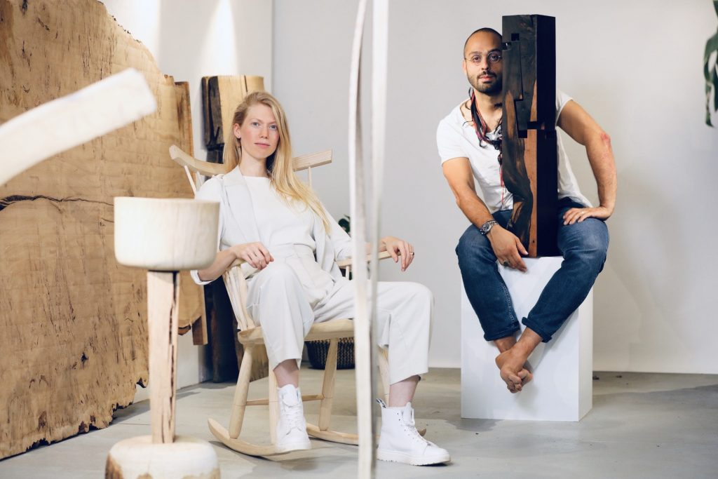 a man and woman in a galllery, dressed in white and surrounded with hand crafted wooden furniture and art works