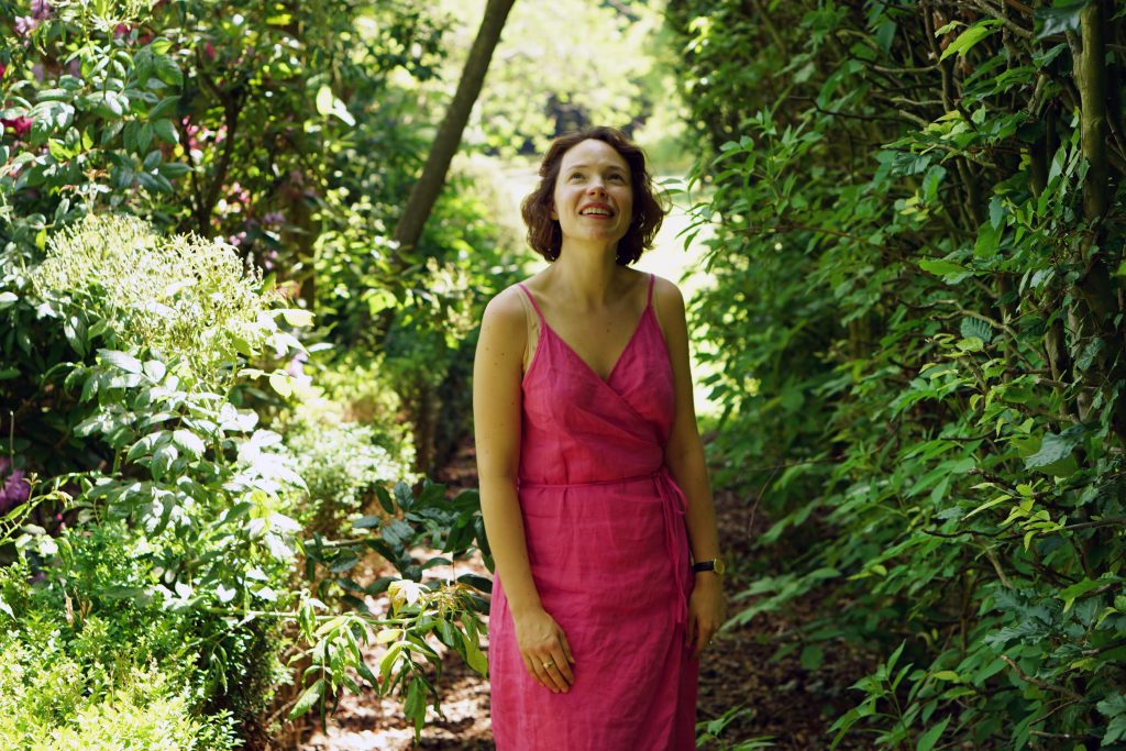 Young woman wearing a deep pink dress in a garden, looking up at trees.