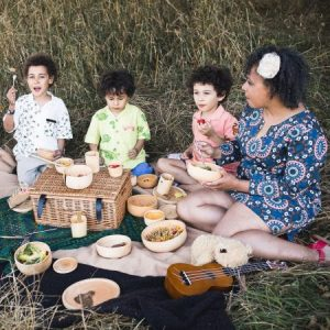 three children and their mum having a picnic in a meadow